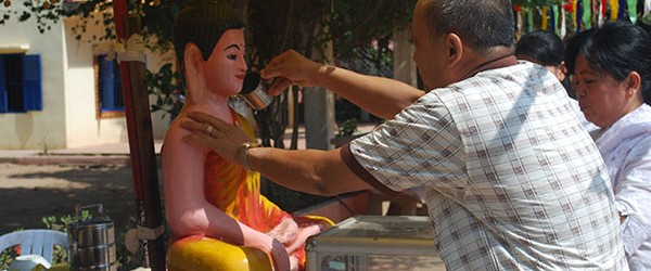 Cambodians clean Buddha statues with perfumed water before Cambodian New Year