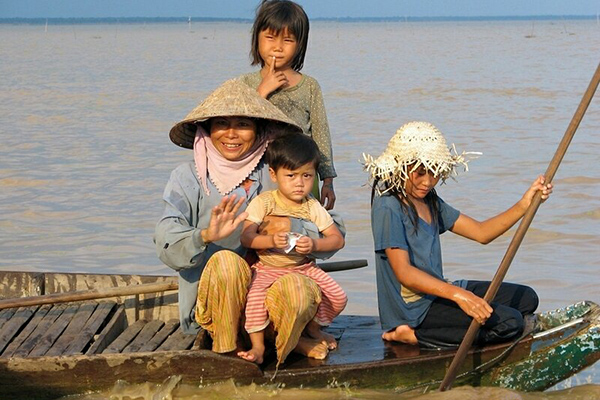 A woman and her daughters on their raft in Kompong Khleang Floating Village