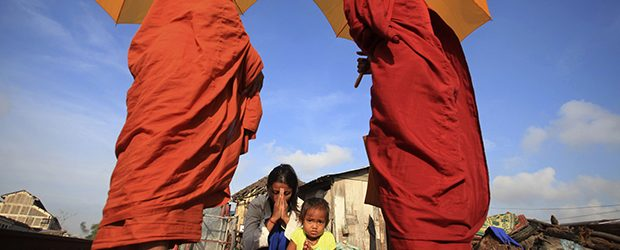 Buddhist monks and the praying woman in Cambodia